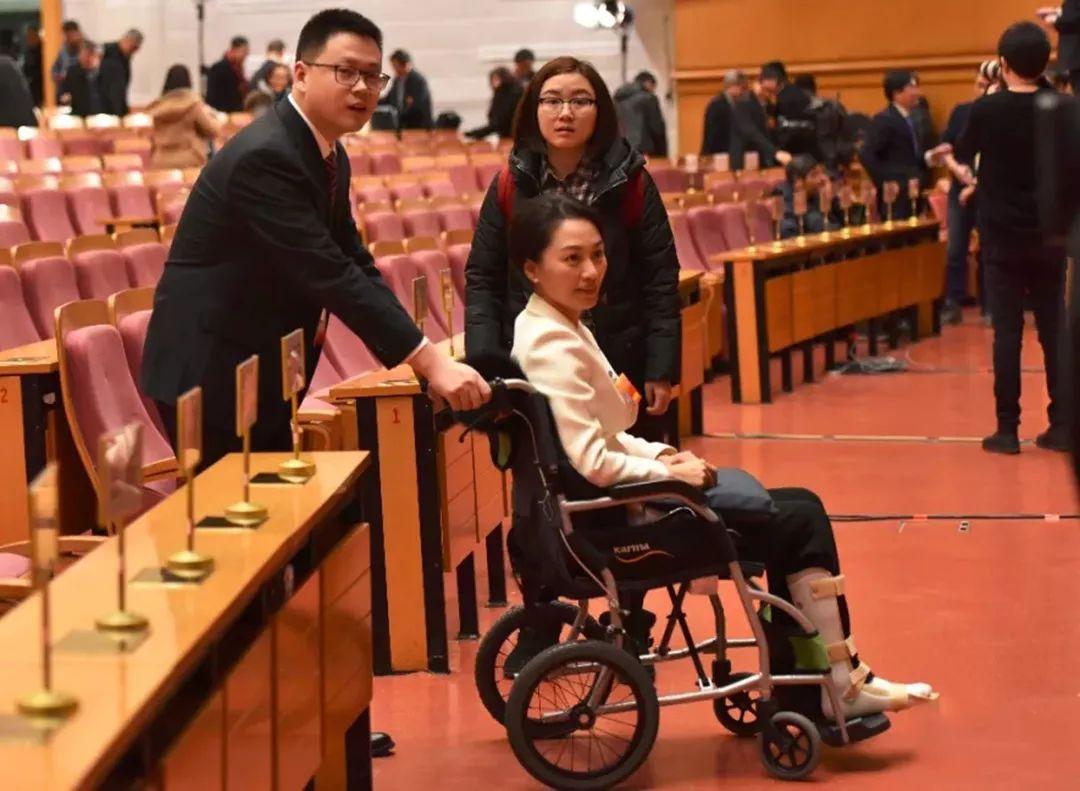 工作人员为政协委员刹住轮椅