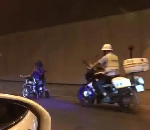老人驾驶电动轮椅在隧道中穿行